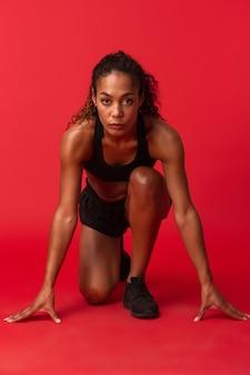 Ritratto di donna afroamericana forte in abbigliamento sportivo nero in esecuzione, isolato sopra la parete rossa