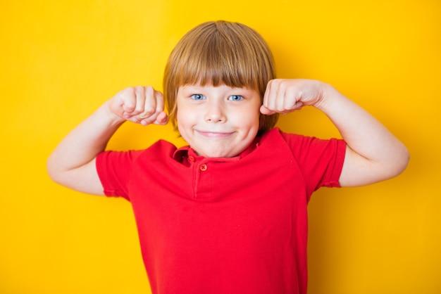 Ritratto di un ragazzo forte che mostra i muscoli delle braccia su giallo