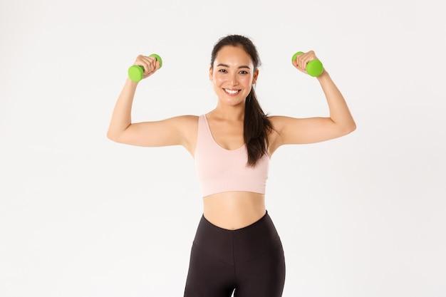 Ritratto di atleta femminile forte e felice, allenamento ragazza asiatica a casa durante il coronavirus, sollevamento manubri per guadagnare muscoli, sfondo bianco.