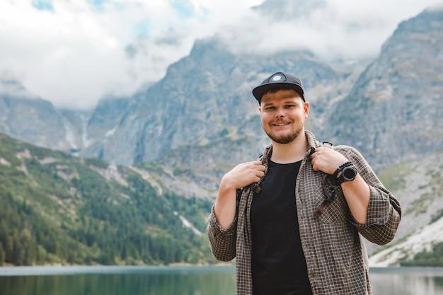 Ritratto di un forte escursionista di fronte al lago in montagna concetto di viaggio