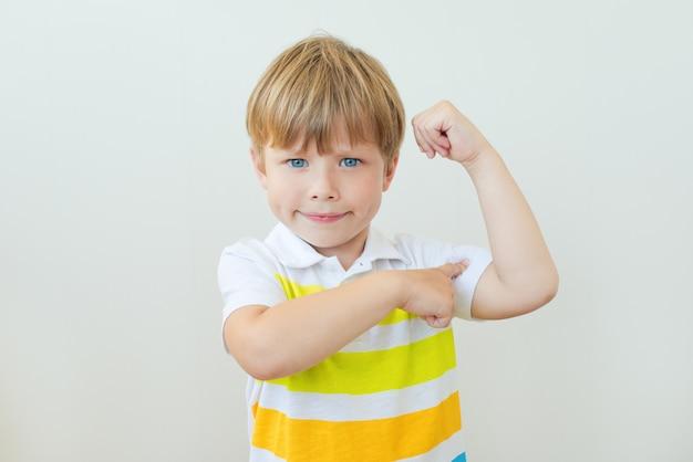 Ritratto di un bambino forte che mostra i muscoli delle sue braccia su bianco