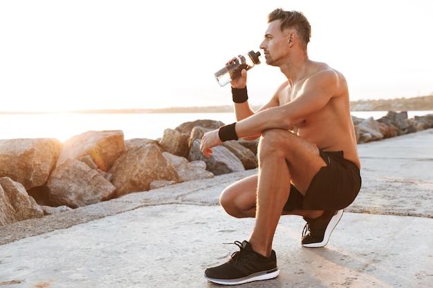 Ritratto di un forte sportivo senza camicia che riposa dopo il jogging