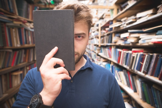 Ritratto di uno studente in piedi nella biblioteca, che copre il viso con un libro nero
