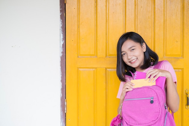 Ragazza dell'allievo del ritratto sullo sfondo della porta gialla con zaini rosa