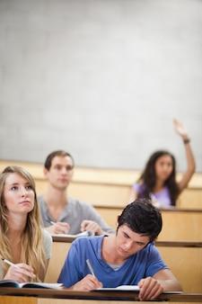 Ritratto di studenti che prendono appunti mentre il loro compagno di classe sta alzando la mano