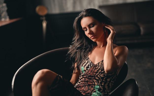 Ritratto di una splendida bella bruna vestita con un vestito che si siede su una poltrona e posa, raddrizzando i suoi lunghi capelli ricci con la mano.