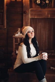 Ritratto di splendida donna dai capelli lunghi con smokey eyes in cappello caldo bere tè caldo o cacao in giornata invernale seduto sotto i fiocchi di neve che cadono