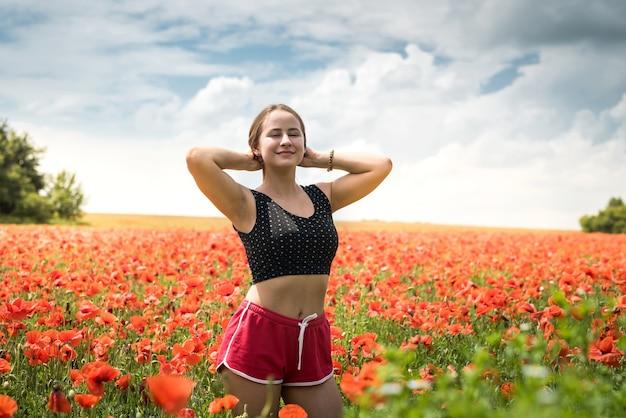 Ritratto di donna splendida in abiti sportivi in posa mentre si cammina in un incredibile campo di papaveri in una calda sera d'estate, godersi la libertà