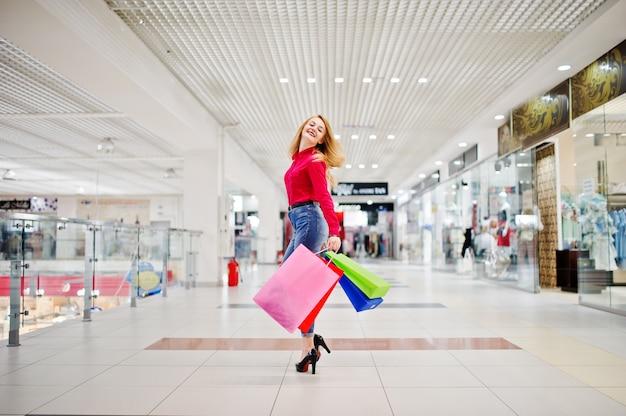 Ritratto di una giovane donna sbalorditiva in camicetta rossa, jeans casual strappati e tacchi alti in posa con le borse della spesa nel centro commerciale.
