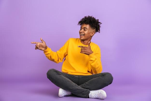 Ritratto di elegante ragazzo afroamericano sorridente e puntando le dita da parte a copyspace mentre è seduto sul pavimento con le gambe incrociate, isolato su sfondo viola