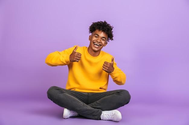 Ritratto di un elegante ragazzo afroamericano che sorride e mostra i pollici mentre è seduto sul pavimento con le gambe incrociate, isolato su sfondo viola