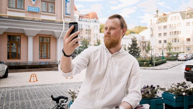 Ritratto di uomo alla moda hipster barbuto utilizzando smartphone sulla strada della città.