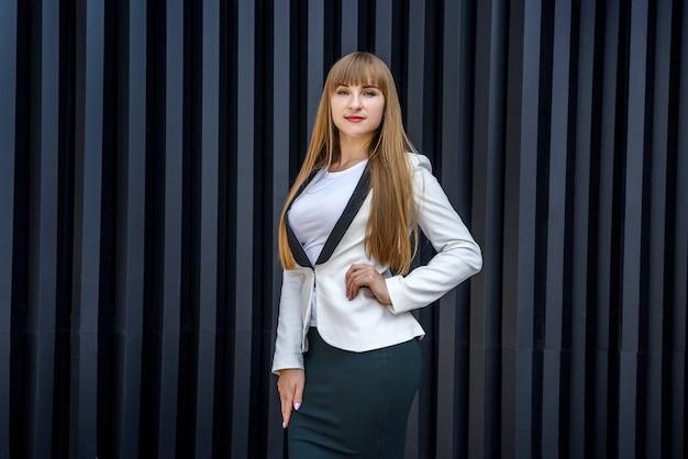 Ritratto di donna d'affari alla moda vicino a sfondo grigio muro