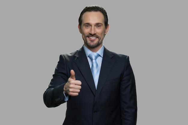 Ritratto dell'uomo d'affari alla moda che dà pollice sul segno. imprenditore di successo che mostra il pollice fino alla telecamera su sfondo grigio. buon lavoro.