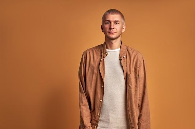 Ritratto del maschio caucasico alla moda isolato su priorità bassa marrone. bel ragazzo giovane sta guardando la fotocamera