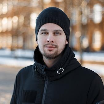 Ritratto di un giovane bello amichevole alla moda con la barba in una giacca nera invernale alla moda in un cappello lavorato a maglia nero su edifici moderni d'epoca. ragazzo alla moda attraente.