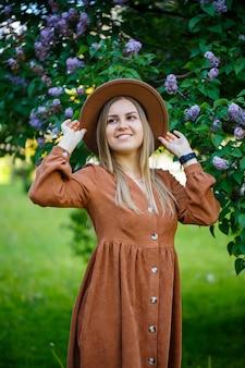 Ritratto di una ragazza alla moda con un cappello marrone e un vestito su uno sfondo lilla. giovane donna di aspetto europeo con un sorriso sul viso