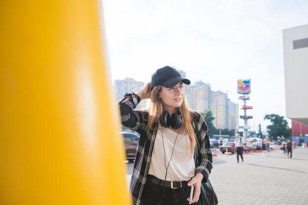 Ritratto di ragazza alla moda all'aperto in abiti di strada sullo sfondo del paesaggio urbano