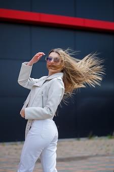 Ritratto di un'elegante ragazza dai capelli lunghi in una camicetta bianca e jeans chiari si erge con un sorriso sullo sfondo di un muro grigio di un edificio in una soleggiata giornata primaverile.