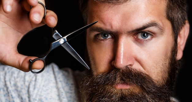 Ritratto di barba uomo alla moda. forbici da barbiere e rasoio, negozio di barbiere. barbiere vintage, rasatura. uomo barbuto, maschio barbuto.