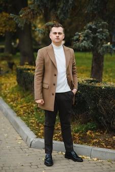 Ritratto di un uomo alla moda con la barba vestito con un cappotto, all'aperto