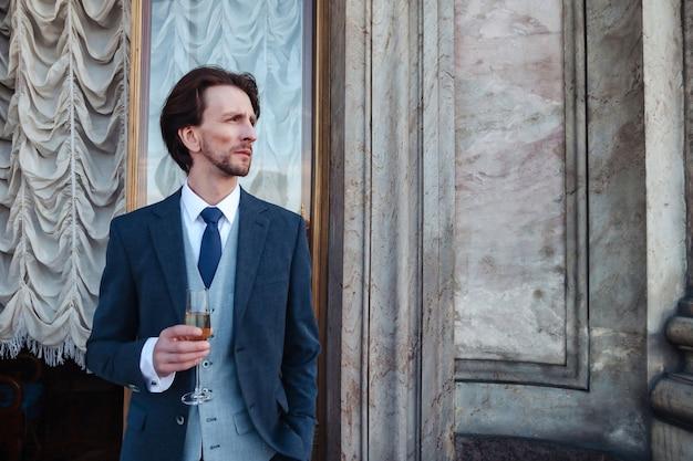 Ritratto uomo elegante con champagne sul balcone del palazzo storico in tuta, guardando lontano. un uomo di mezza età innamorato trascorre il fine settimana. concetto di appuntamenti romantici e sorprese. copia spazio