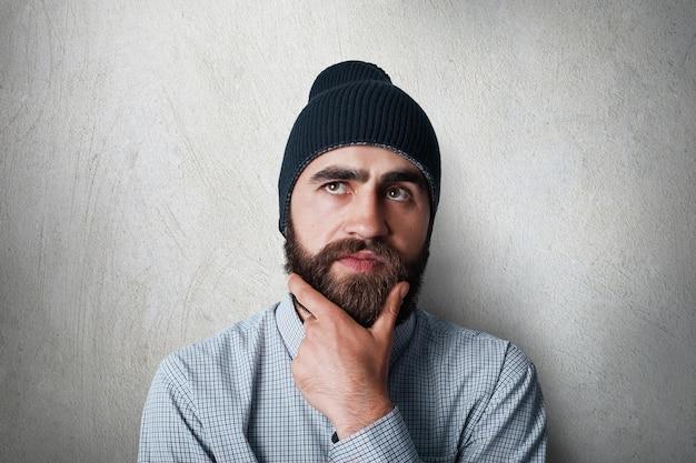 Ritratto di uomo elegante con folta barba nera che indossa cappello nero e camicia casual a quadri