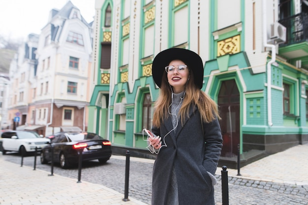 Ritratto di un'elegante ragazza positiva che mette su una bella architettura e ascolta la musica.