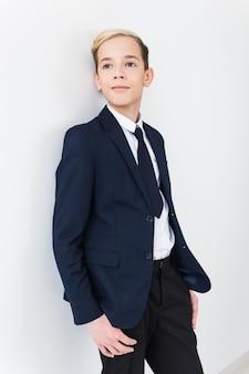 Ritratto dell'adolescente del ragazzo di scuola alla moda in camicia bianca e giacca contro la superficie bianca.