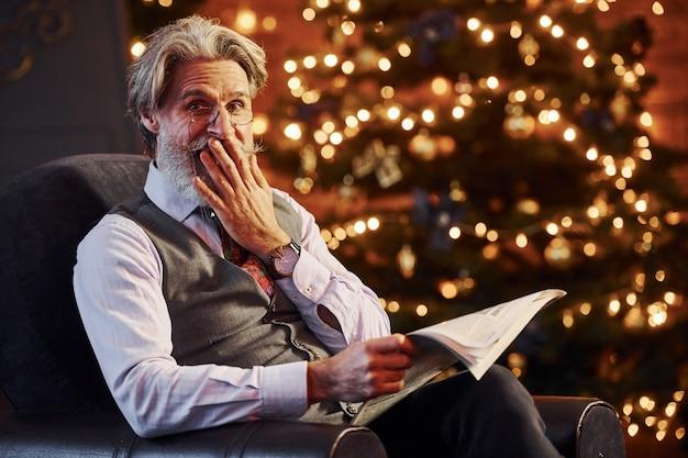 Il ritratto dell'anziano alla moda con capelli grigi e la barba è nella stanza decorata di natale con il libro in mani.