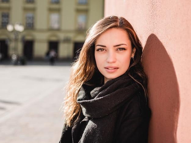 Ritratto di una donna felice sorridente alla moda che cammina per strada, umore positivo, la ragazza si gode i fine settimana