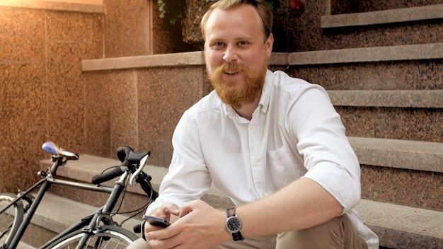 Ritratto dell'uomo sorridente alla moda con la barba che si siede sulle scale di pietra sulla via della città al tramonto.