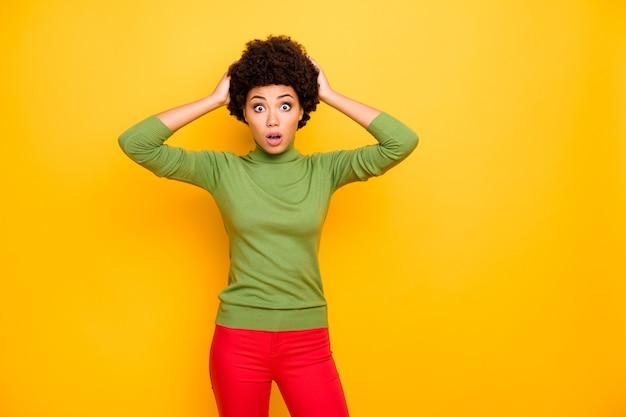 Ritratto di donna stupita alla moda alla moda che tiene la sua testa in pantaloni rossi paura della diffusione di notizie false.