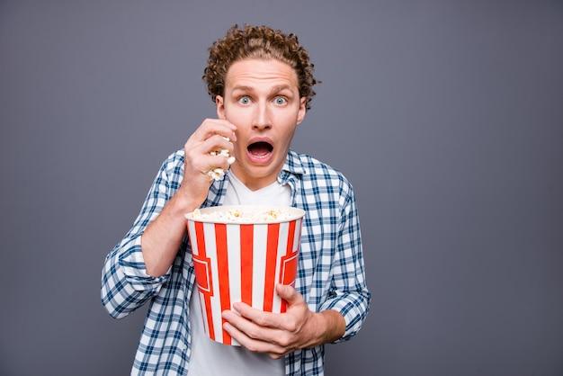 Ritratto di uomo preoccupato alla moda che tiene scatola di popcorn mangiare