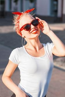 Ritratto di una ragazza alla moda giovane hipster con occhiali da sole in città