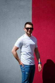 Ritratto di un giovane alla moda, un uomo vestito con una maglietta bianca vuota in piedi su uno sfondo grigio e rosso della parete. stile urbano di vestiti, immagine alla moda moderna. moda maschile