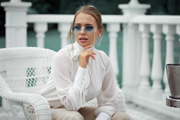 Ritratto di una giovane donna elegante che posa con gli occhiali da sole, seduta su una sedia all'aria aperta