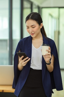 Ritratto di una donna d'affari di successo in piedi in ufficio con una tazza di caffè e un sms al telefono, messaggio, contatto, uso del telefono