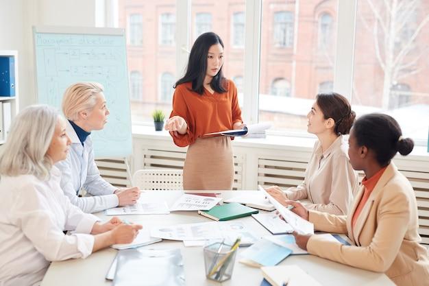 Ritratto di imprenditrice asiatica di successo che presenta il piano di progetto a un gruppo di colleghi di sesso femminile in piedi dalla lavagna durante la riunione nella sala conferenze