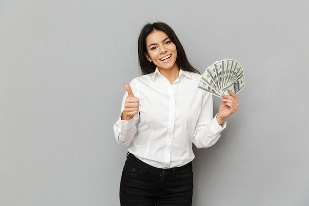 Ritratto di donna castana di successo che indossa abito formale che tiene un sacco di dollari in mano e che mostra il pollice in su, isolato sopra il muro grigio