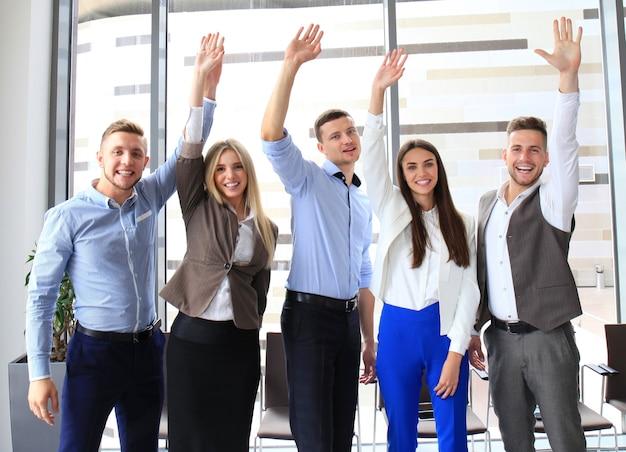 Ritratto di gruppo aziendale di successo che agita le mani in ufficio