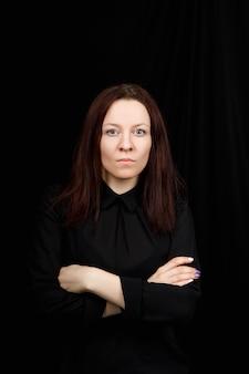 Ritratto di donna d'affari di successo in una camicia nera con le mani incrociate su sfondo nero.