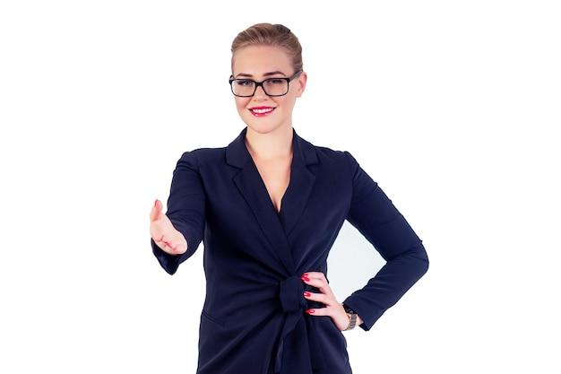 Ritratto di donna d'affari di successo occhiali acconciatura bionda trucco perfetto labbra rosse in elegante abito nero dà una mano per un isolato bianco studio gesto di benvenuto stretta di mano. idea di saluto
