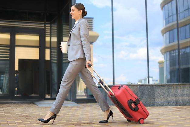 Ritratto di donna d'affari di successo che va in tuta tirando i bagagli mentre si cammina all'aperto.