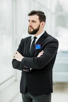 Ritratto di imprenditore di successo in piedi vicino a una finestra in ufficio luminoso.