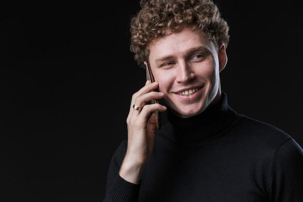 Ritratto di un allegro giovane attraente uomo d'affari dai capelli ricci di successo in piedi davanti al muro nero, parlando al cellulare