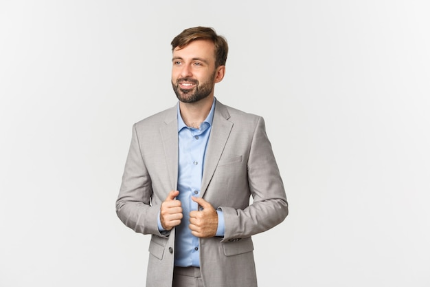 Ritratto di imprenditore di successo e fiducioso in abito grigio e camicia blu, sorridendo soddisfatto e guardando a sinistra, in piedi su sfondo bianco.