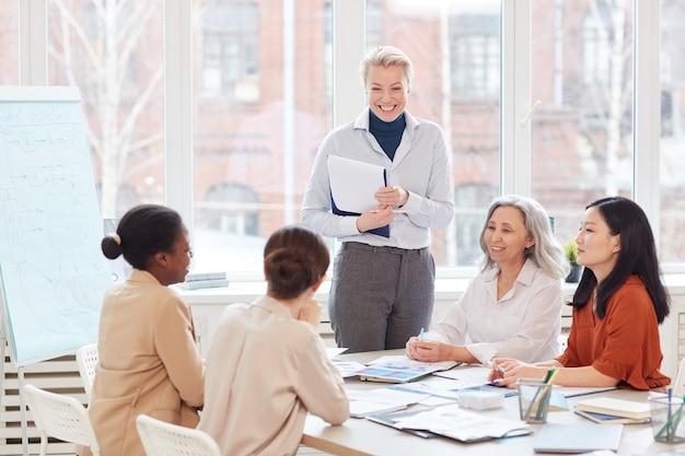 Ritratto del capo femminile di successo che sorride felicemente guardando un gruppo di colleghi durante la riunione nell'ufficio bianco moderno