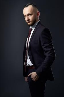 Ritratto di un uomo d'affari di successo maschile su uno sfondo scuro