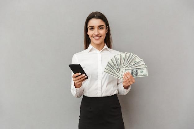 Ritratto di donna di successo ufficio con lunghi capelli castani in bianco e nero indossare sorridente mentre si tiene in mano il fan di soldi e smartphone, isolato sopra il muro grigio